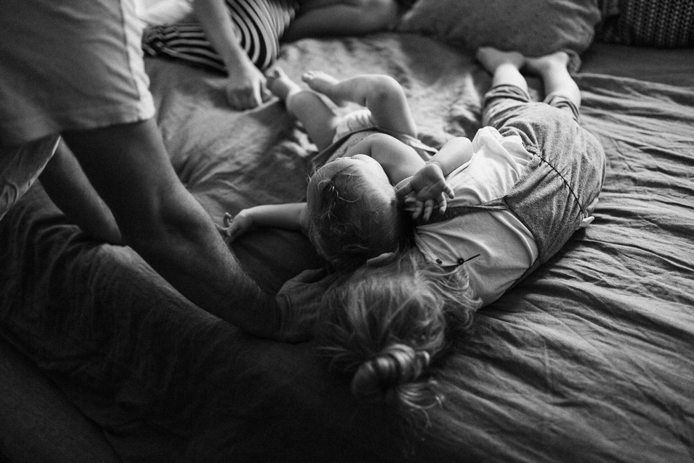 black-and-white-candid-photo-of-family-on-bed-during-in-home-session-with-jen-fairchild-photography-salt-lake-city-utah