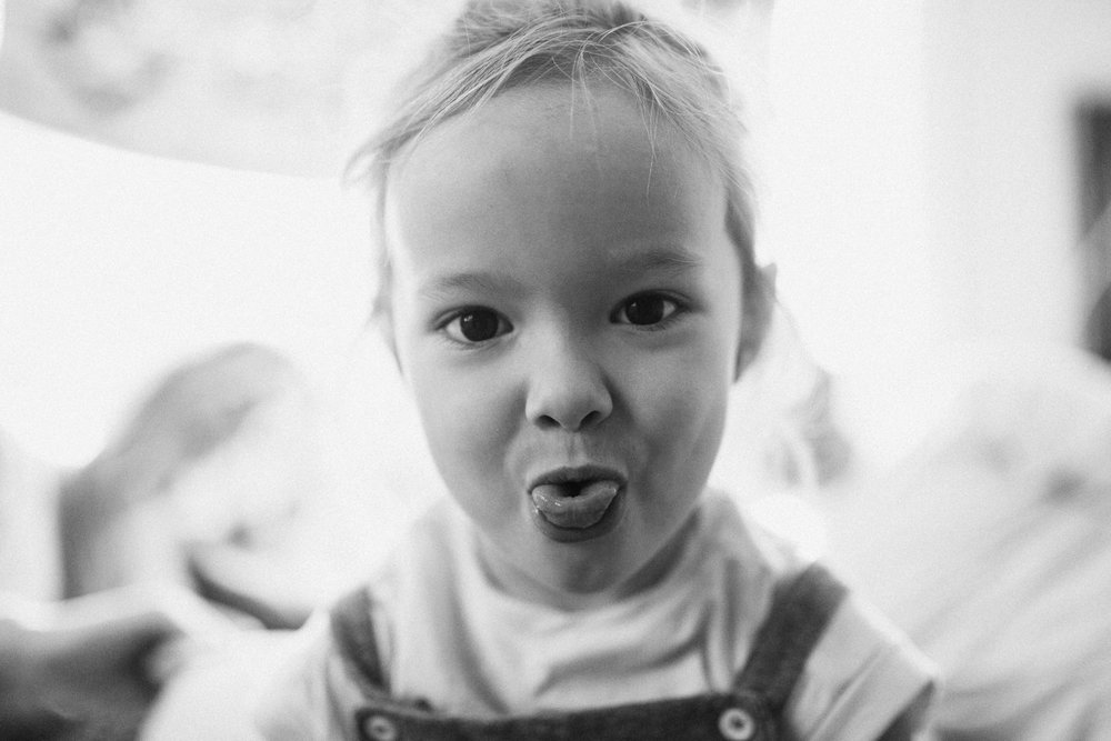 candid-black-and-white-photo-of-little-girl-looking-at-camera-sticking-out-tongue-slc-utah