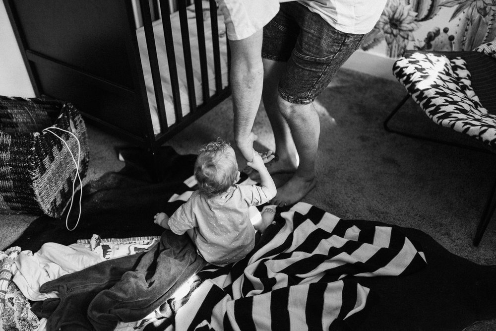 black-and-white-photo-of-father-helping-daughter-stand-up-in-nursery-slc-utah