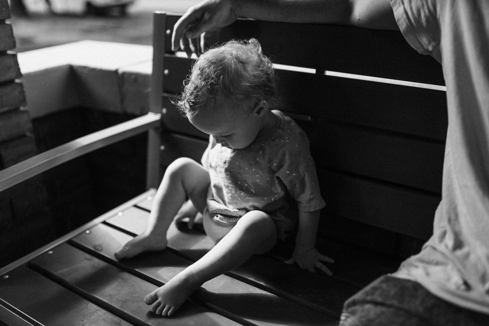black-and-white-photo-of-child-sitting-on-bench-outside-salt-lake-city-utah