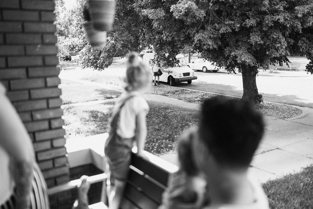 candid-black-and-white-photo-of-little-girl-watching-mailman-during-in-home-session-with-jen-fairchild-in-salt-lake-city-utah