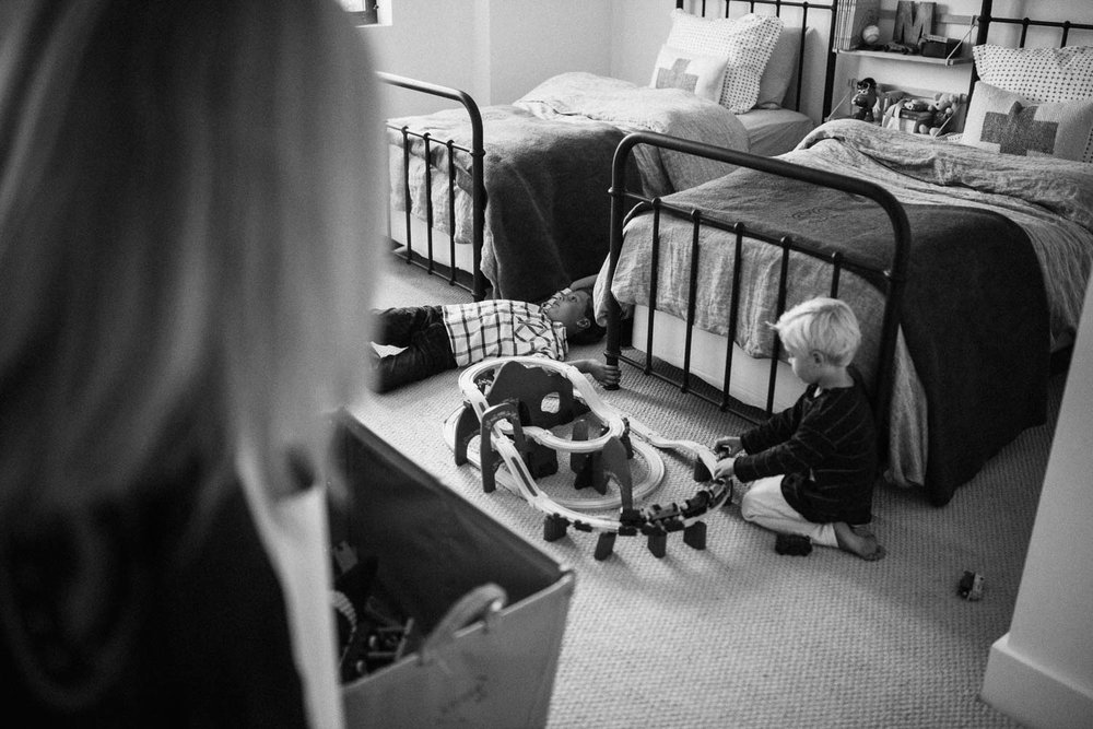 candid-black-and-white-family-photo-playing-with-train-tracks-during-in-home-session-with-jen-fairchild-in-encinitas-ca