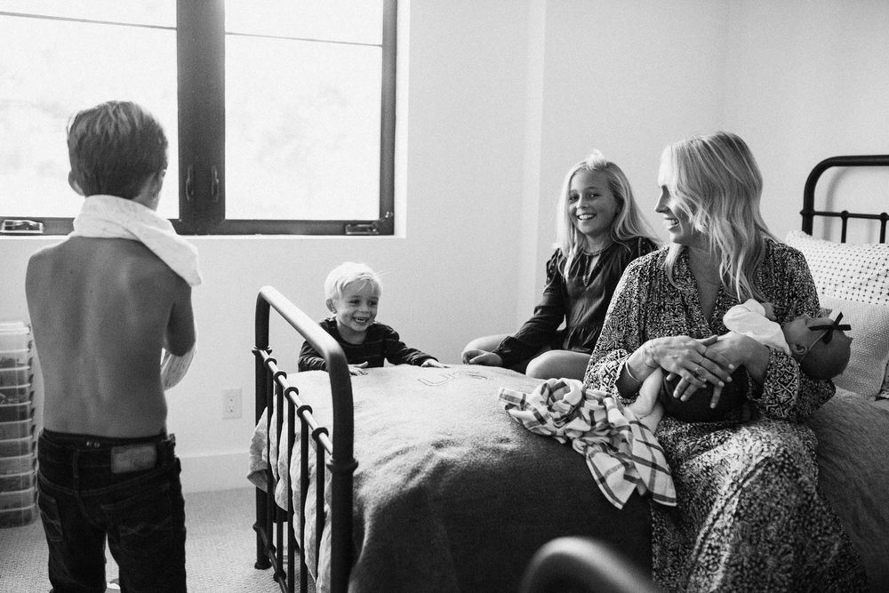 natural-and-artistic-black-and-white-family-photo-sitting-on-bed-together-during-in-home-family-session-in-encinitas-california