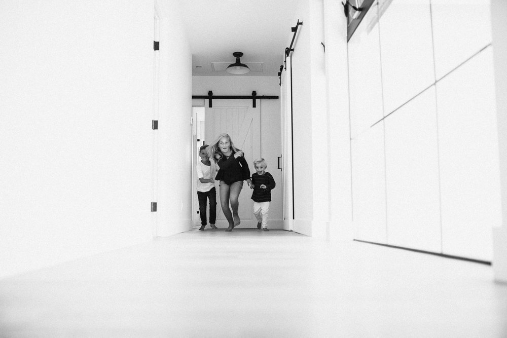 candid-black-and-white-photo-of-children-running-down-hallway-in-encinitas-ca