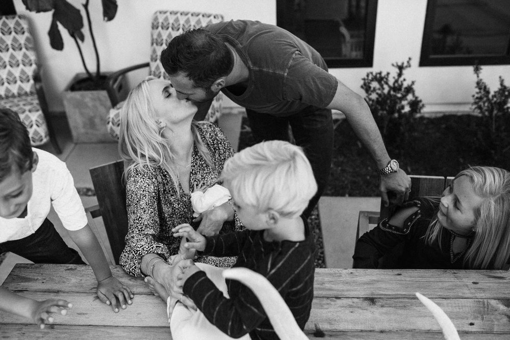 candid-black-and-white-family-photo-with-parents-kissing-during-in-home-session-with-jen-fairchild-photography-in-encinitas-california