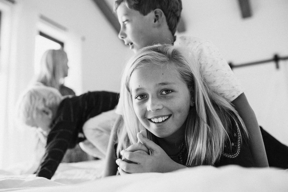 black-and-white-photo-of-children-doggy-piling-on-bed-encinitas-ca