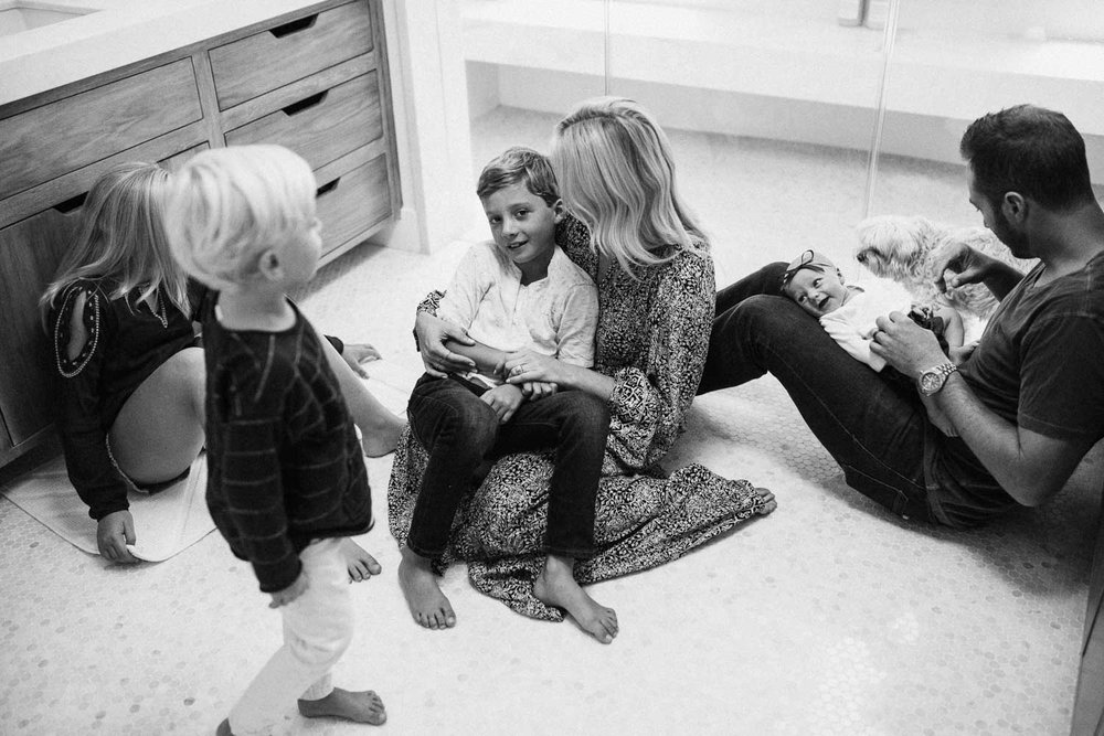 candid-black-and-white-photo-of-family-sitting-on-bathroom-floor-during-in-home-session-with-jen-fairchild-photography-in-encinitas-california