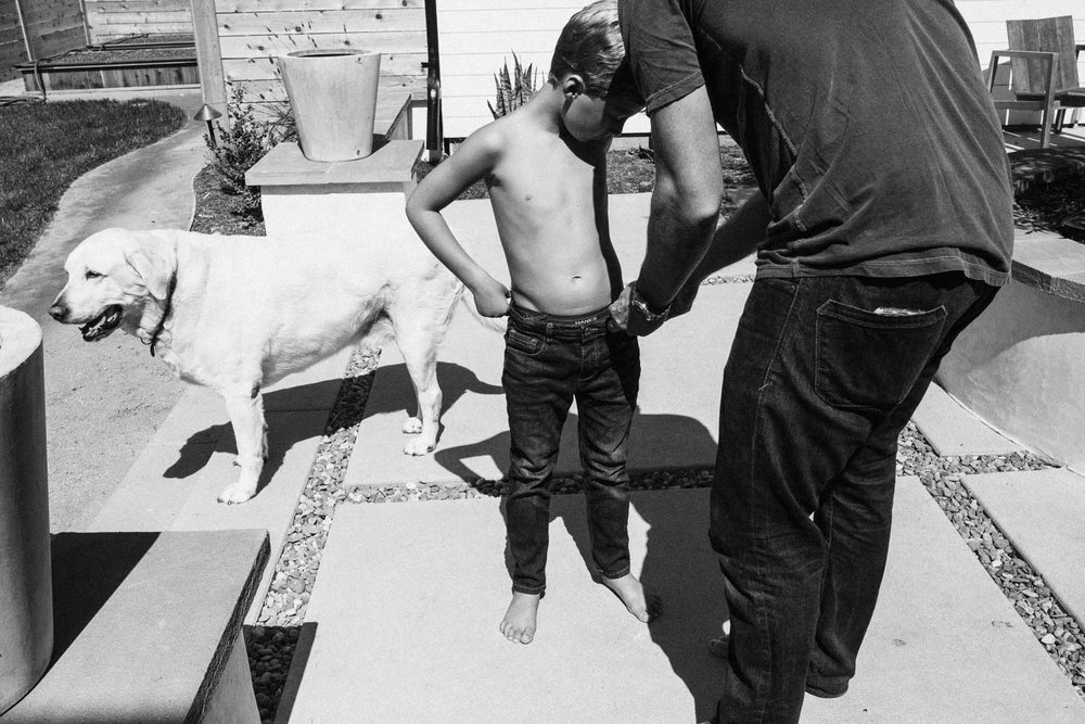 candid-black-and-white-photo-of-father-helping-son-in-backyard-with-dog-encinita-ca