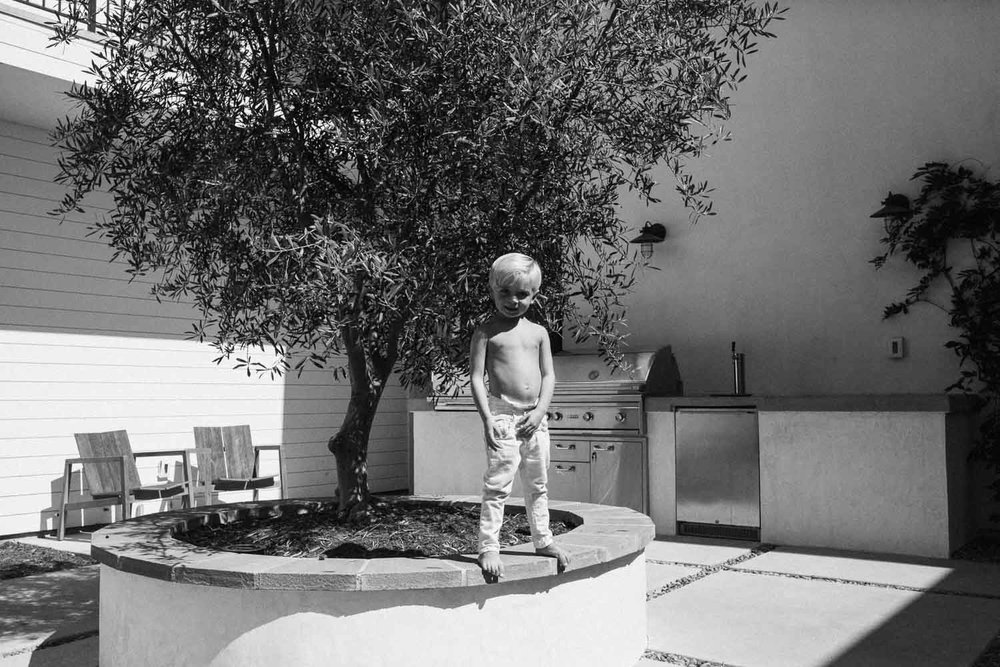 candid-black-and-white-photo-of-little-blonde-boy-standing-on-ledge-in-back-yard-encinita-california