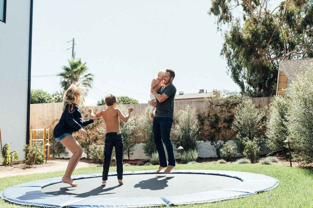 natural-and-artistic-photo-of-father-jumping-on-trampoline-with-children-encinita-ca