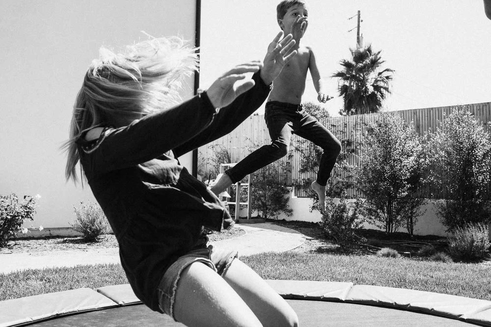 candid-black-and-white-photo-of-brother-and-sister-jumping-on-trampoline-encinita-ca