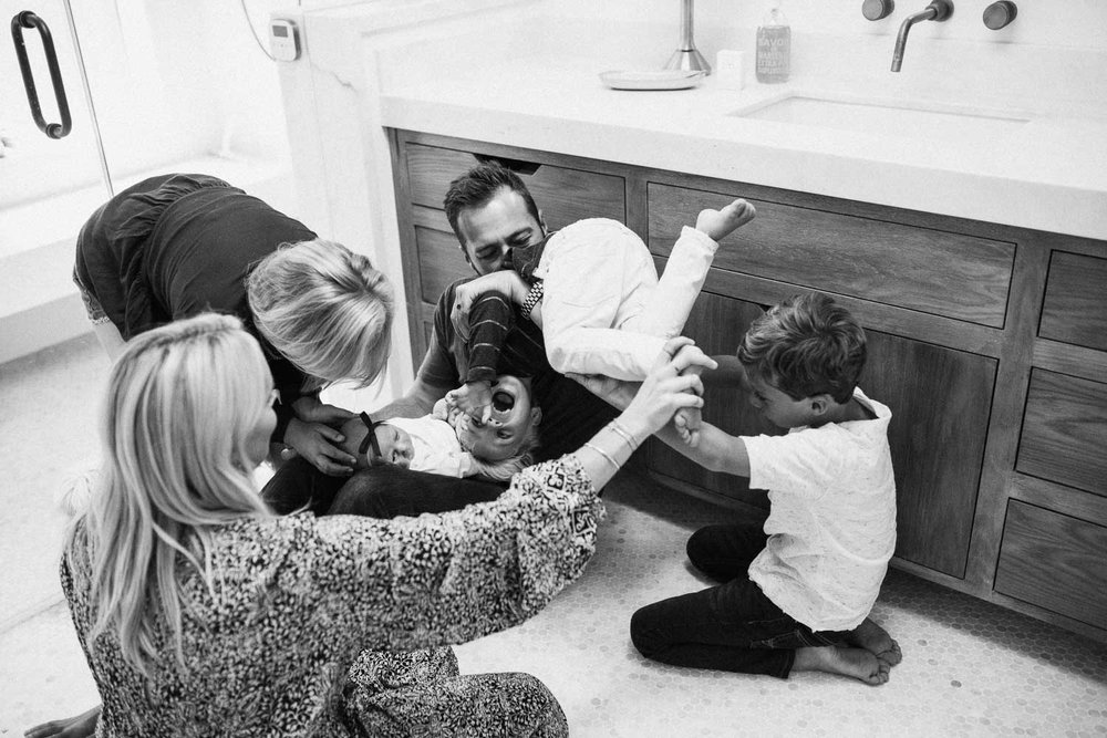 natural-and-artistic-black-and-white-photo-of-family-on-bathroom-floor-encinita-ca