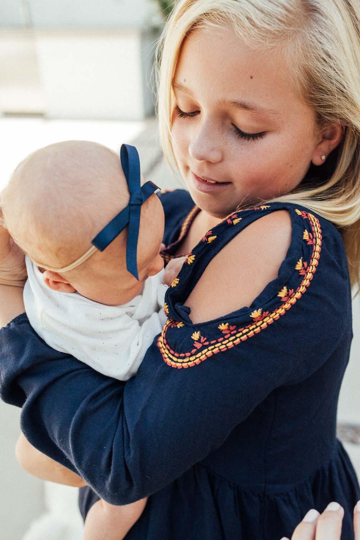 natural-and-artistic-photo-of-girl-holding-baby-sister-encinita-ca