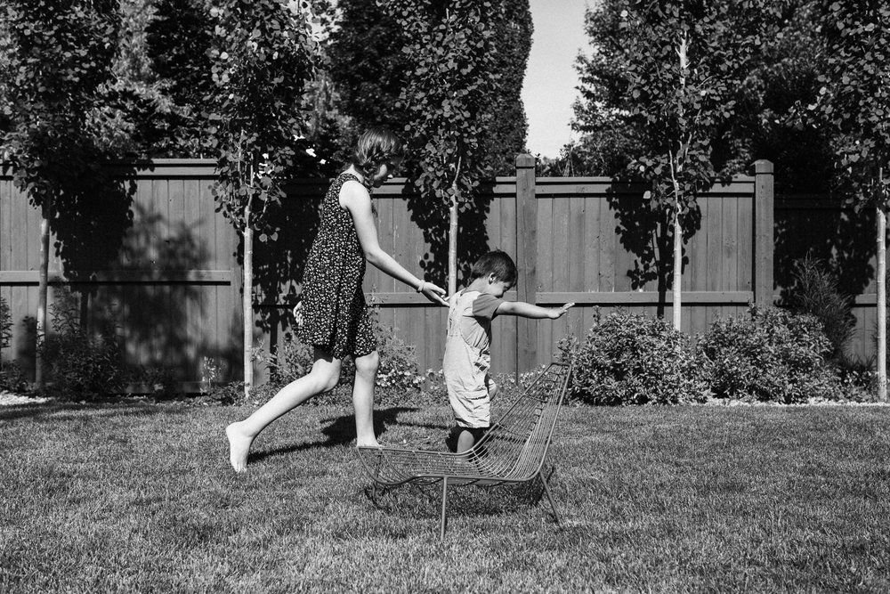 natural-and-artistic-black-and-white-photo-of-brother-and-sister-walking-in-backyard-salt-lake-city-utah