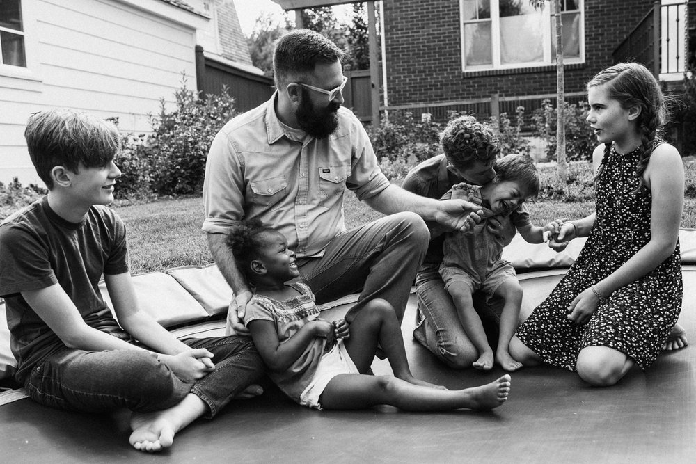 candid-black-and-white-family-photo-sitting-on-trampoline-during-in-home-session-with-jen-fairchild-in-salt-lake-city-utah