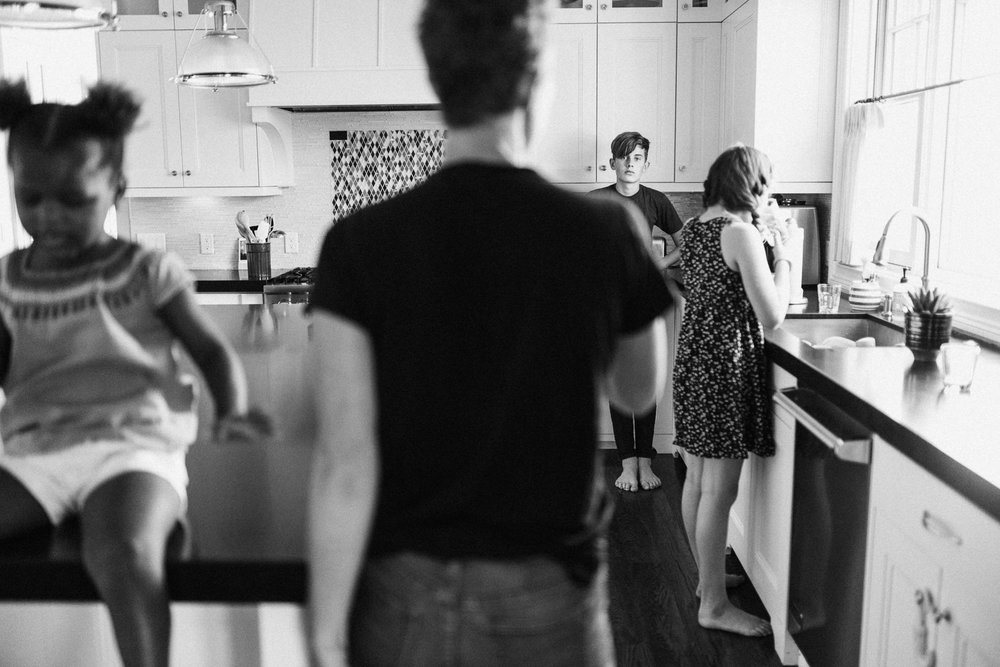candid-black-and-white-family-photo-in-kitchen-during-in-home-session-with-jen-fairchild-in-salt-lake-city-utah