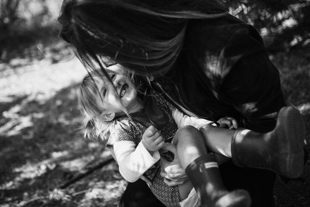 candid-black-and-white-photo-of-mother-holding-laughing-daughter-during-at-home-session-with-jen-fairchild-photography-slc-ca