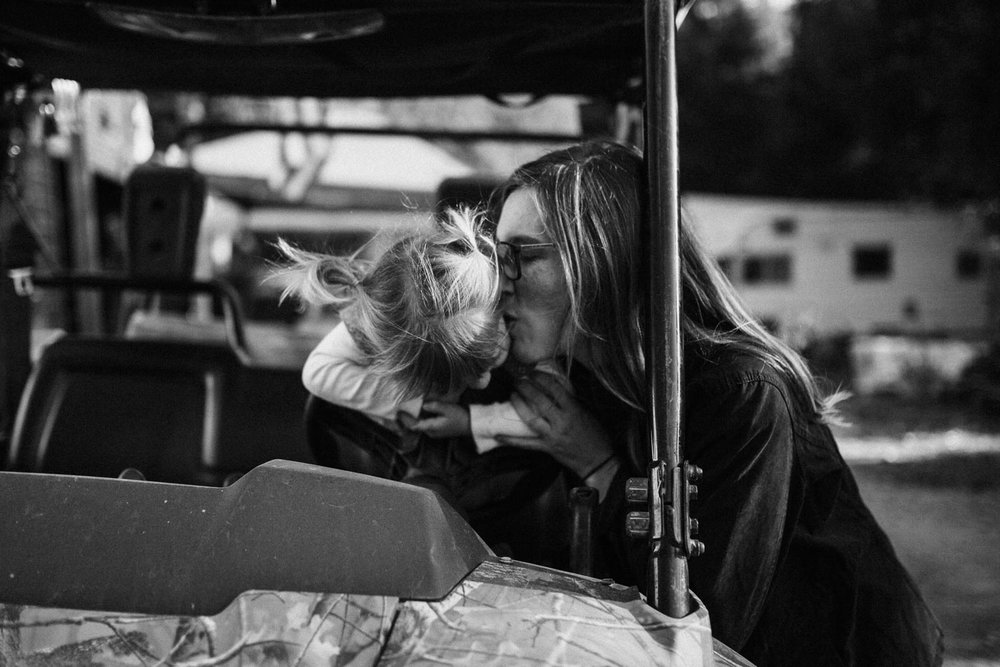 candid-black-and-white-intimate-moment-of-mother-kissing-daughters-cheek-garberville-ca