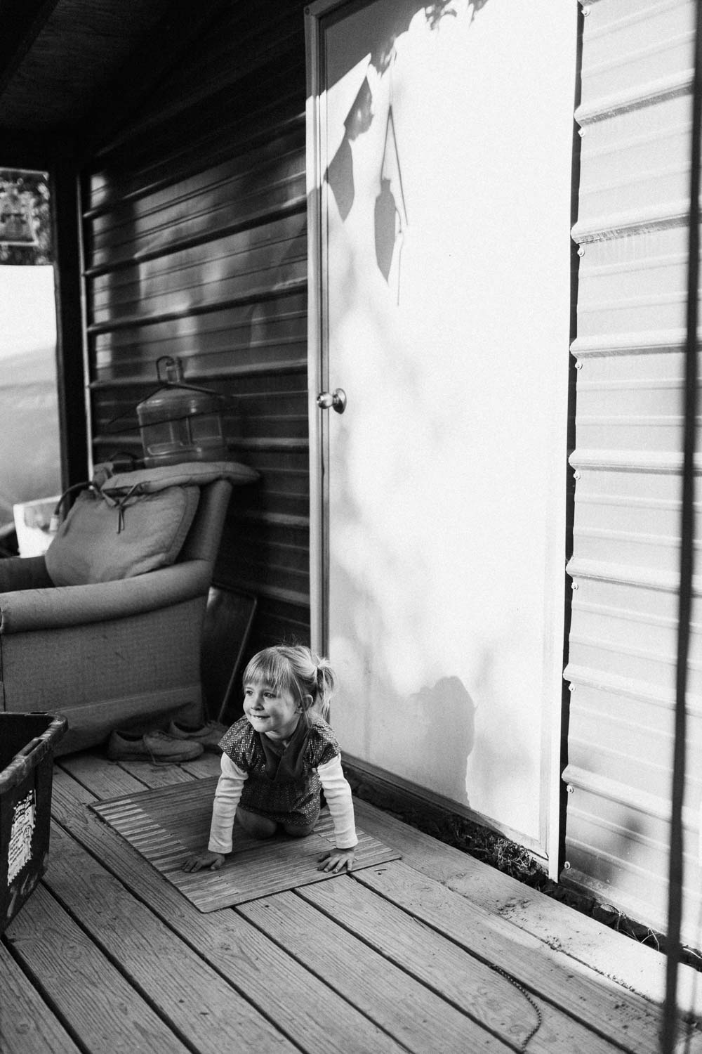 candid-black-and-white-playful-moment-crawling-on-porch-on-weed-farm-in-san-francisco-california