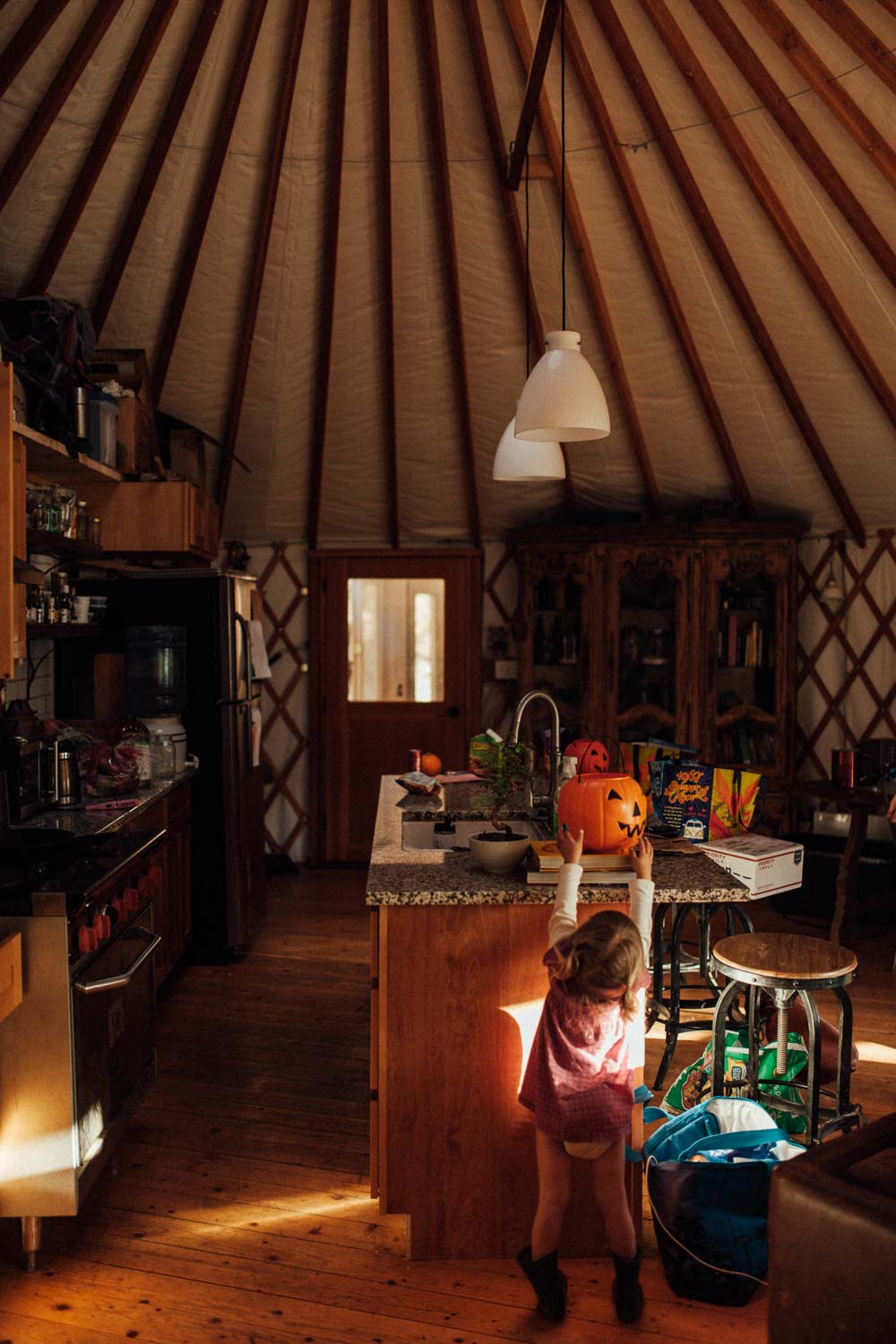 natural-and-artistic-moment-in-yurt-reaching-for-halloween-candy-benbow-ca