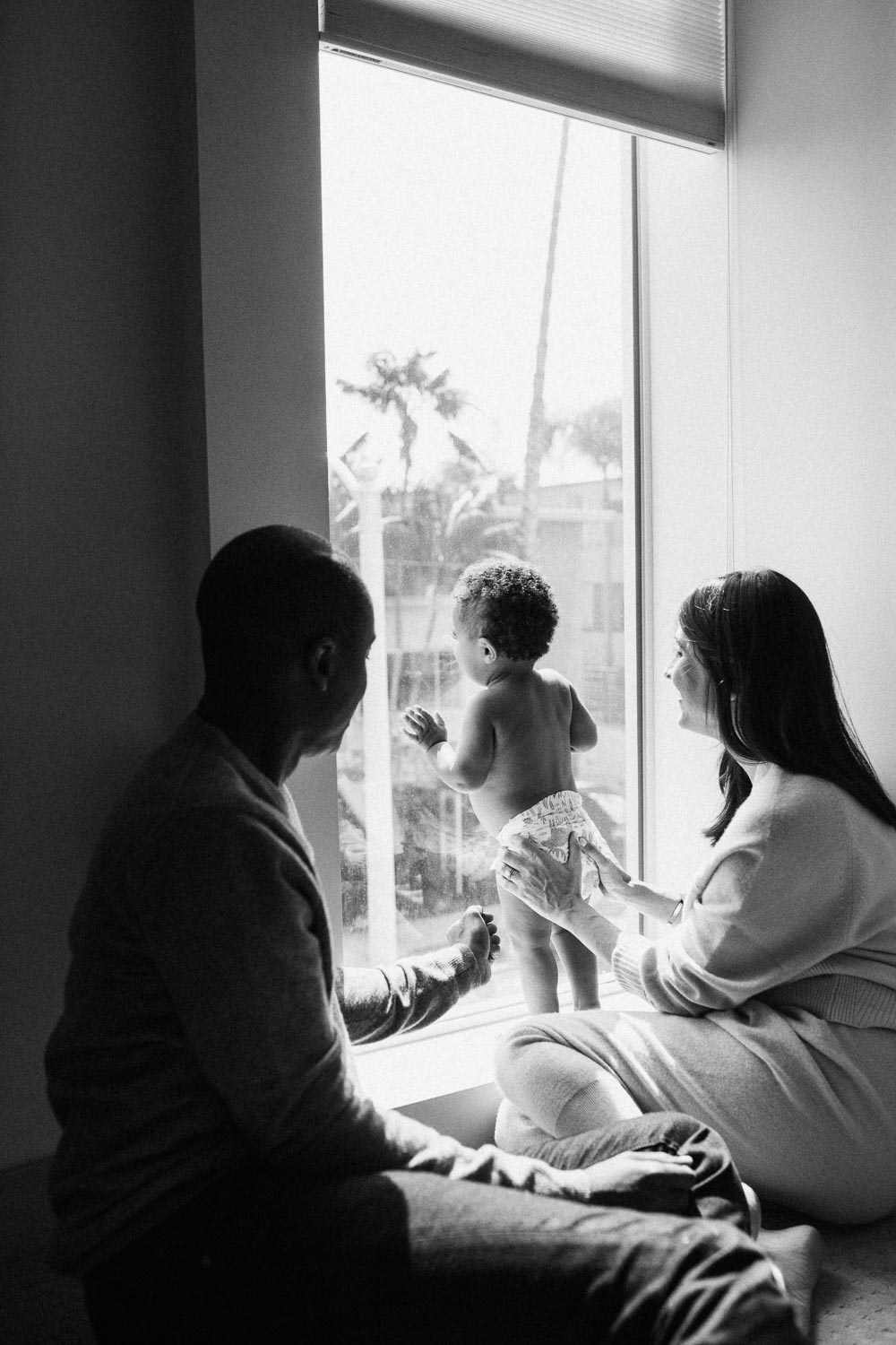 natural-and-artistic-black-and-white-photo-of-family-looking-out-window-in-los-angeles-california