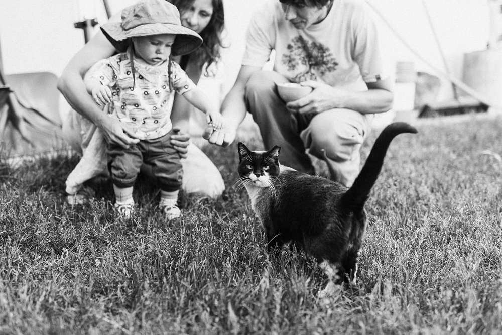 candid-black-and-white-family-photo-outside-with-crosseyed-cat-looking-at-camera