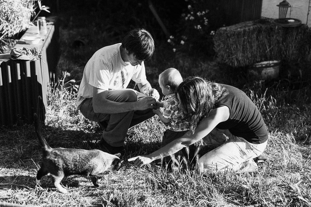 candid-black-and-white-photo-of-family-in-backyard-with-pet-cat-holladay-utah