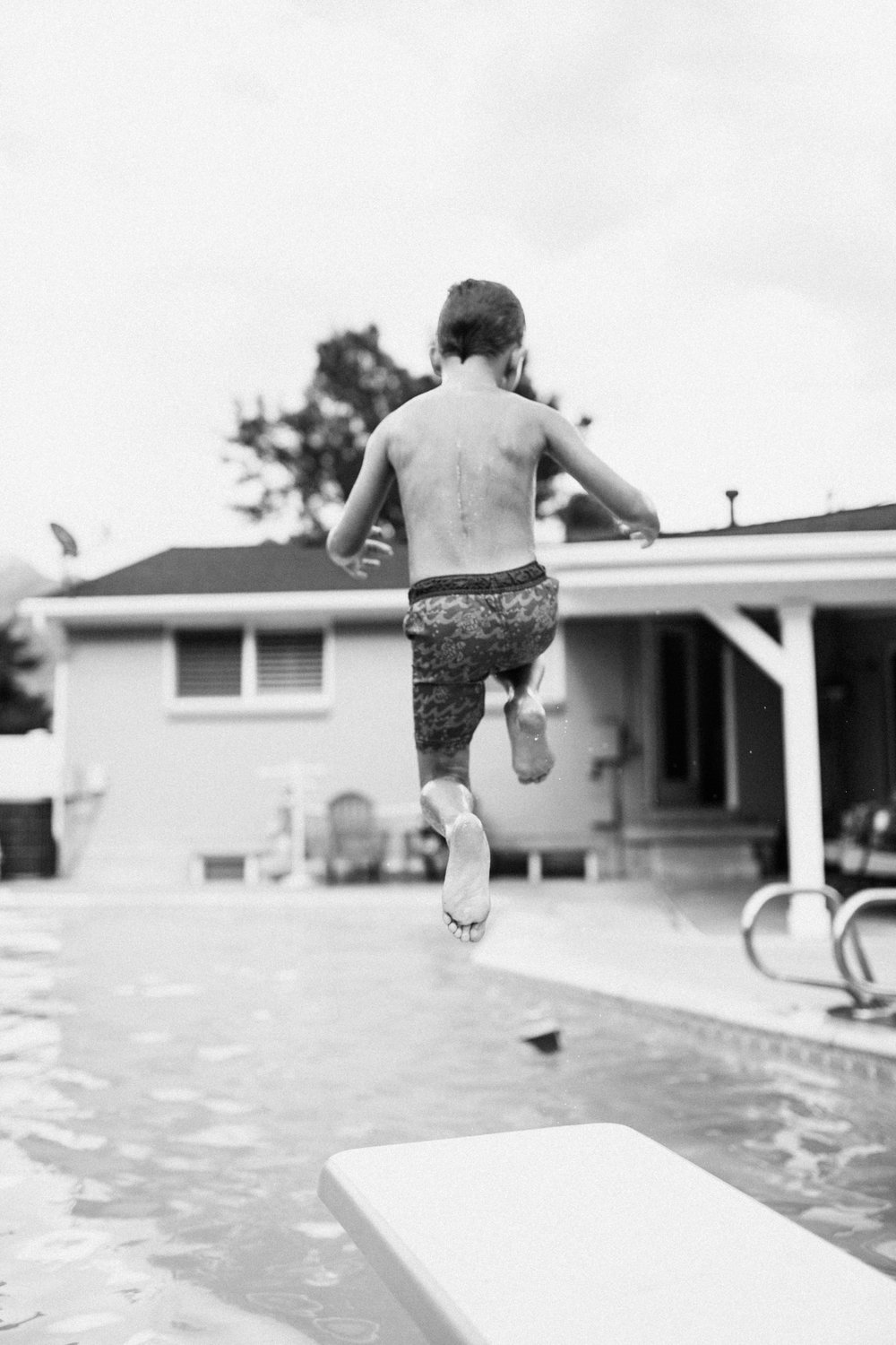candid-photo-black-and-white-of-young-boy-jumping-off-diving-board-bountiful-utah