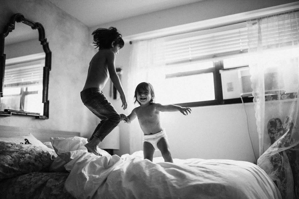 black-and-white-candid-nostalgic-photo-of-brothers-jumping-on-bed-during-in-home-session-with-jen-fairchild-photography-new-york-city
