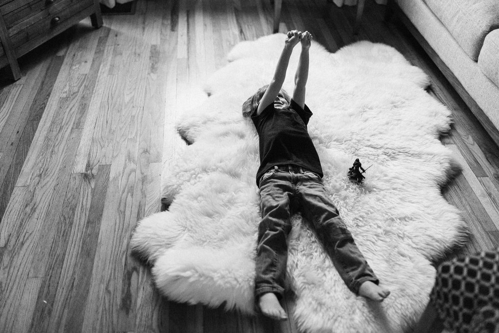 candid-black-and-white-photo-boy-laying-on-sheep-skin-arms-up-in-the-air-salt-lake-utah