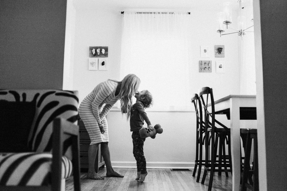 candid-black-and-white-photo-of-mother-and-son-kissing-in-kitchen-slc-utah