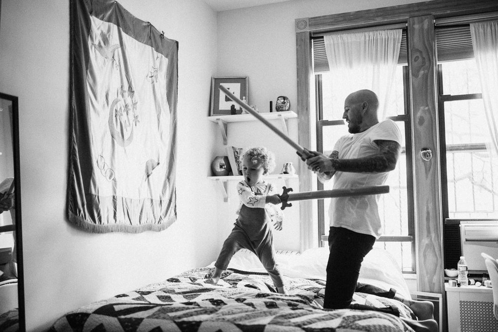 candid-black-and-white-playful-exciting-sword-fight-between-father-and-son-holladay-utah