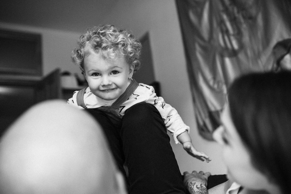 candid-black-and-white-portrait-cute-curly-haired-boy-smiling-at-camera-holladay-ut