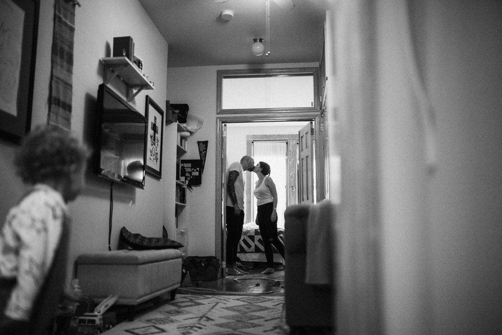 natural-and-artistic-black-and-white-intimate-photo-of-little-boy-watching-mom-and-dad-kiss-during-in-home-session-with-jen-fairchild-photography