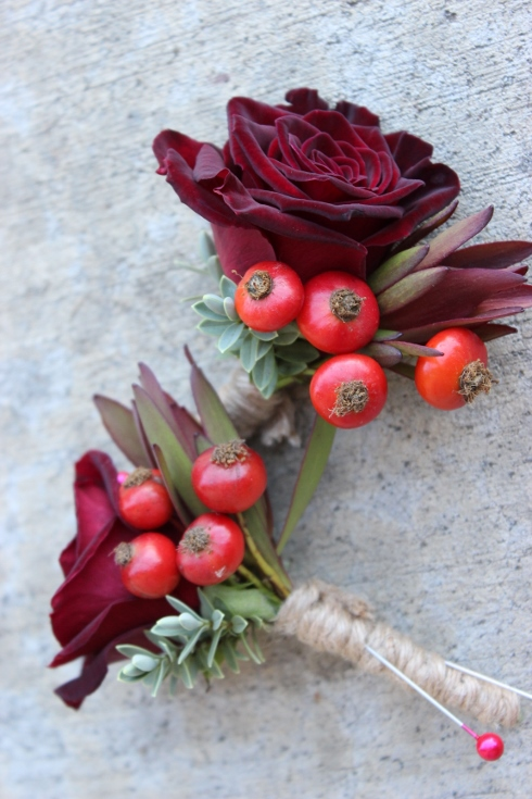 black rose boutonniere corsage with red rose hips berries