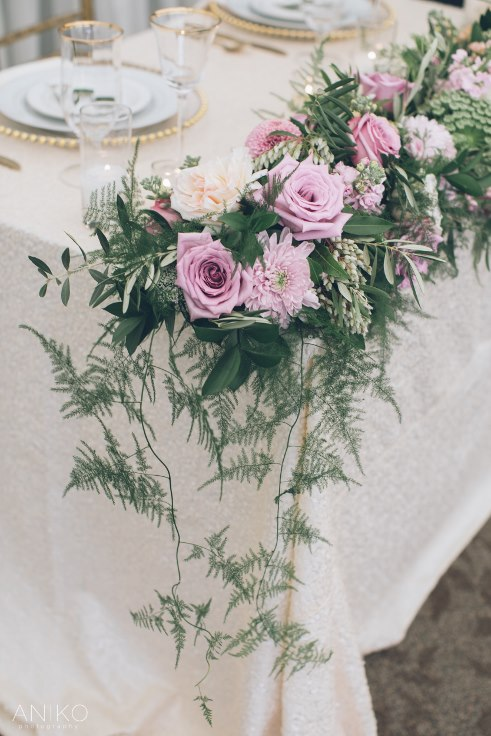 sophisticated floral designs sweetheart table flowers lavender purple garland foliage vines