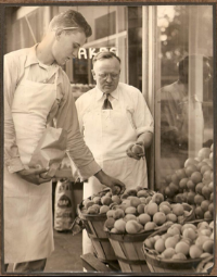 ashley clague inspects peaches at clague's grocery & meat market, circa 1960