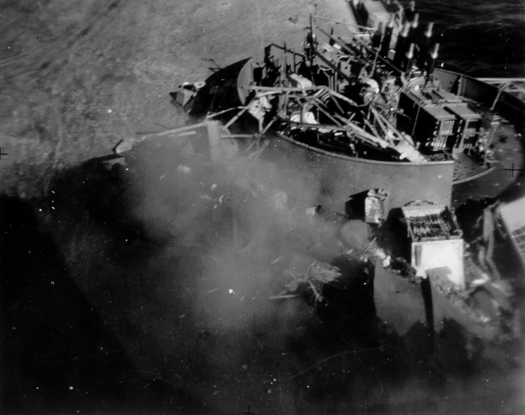 "Blast effect ... the 'Starboard 1' forward Pom Pom gun sits jammed by the collapsed 'Jumbo' crane as the wreckage of ""S2"" Pom Pom mount still smoulders in the foreground. It had probably been struck by a contact-fused German General Purpose bomb."