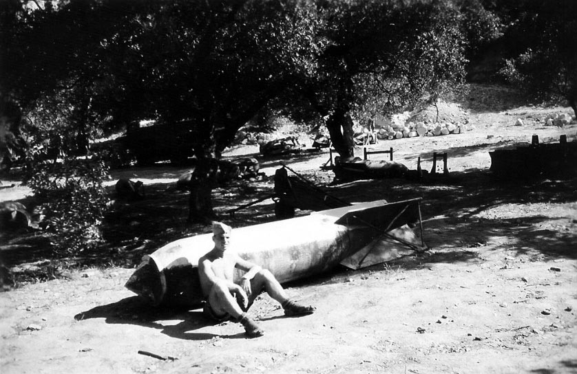 A Luftwaffe airman sits resting against a 1000kg (2200lb) bomb while stationed at an airfield in the Crete theatre.