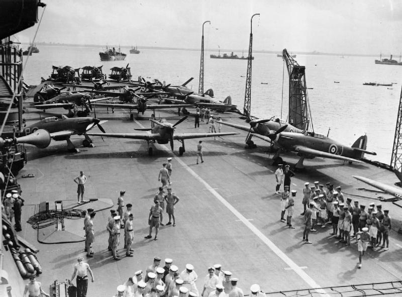 Hawker Sea Hurricanes and Fairey Albacores on the flight deck of HMS INDOMITABLE during a Malta convoy. Note the radio masts in the upright position and the crane on the edge of the deck.