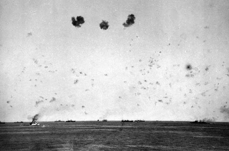 11 August: The loss of HMS EAGLE and the first air attacks: A general view of the convoy under air attack showing the intense anti-aircraft barrage put up by the escorts. The battleship HMS RODNEY is on the left and the cruiser HMS MANCHESTER on the right.