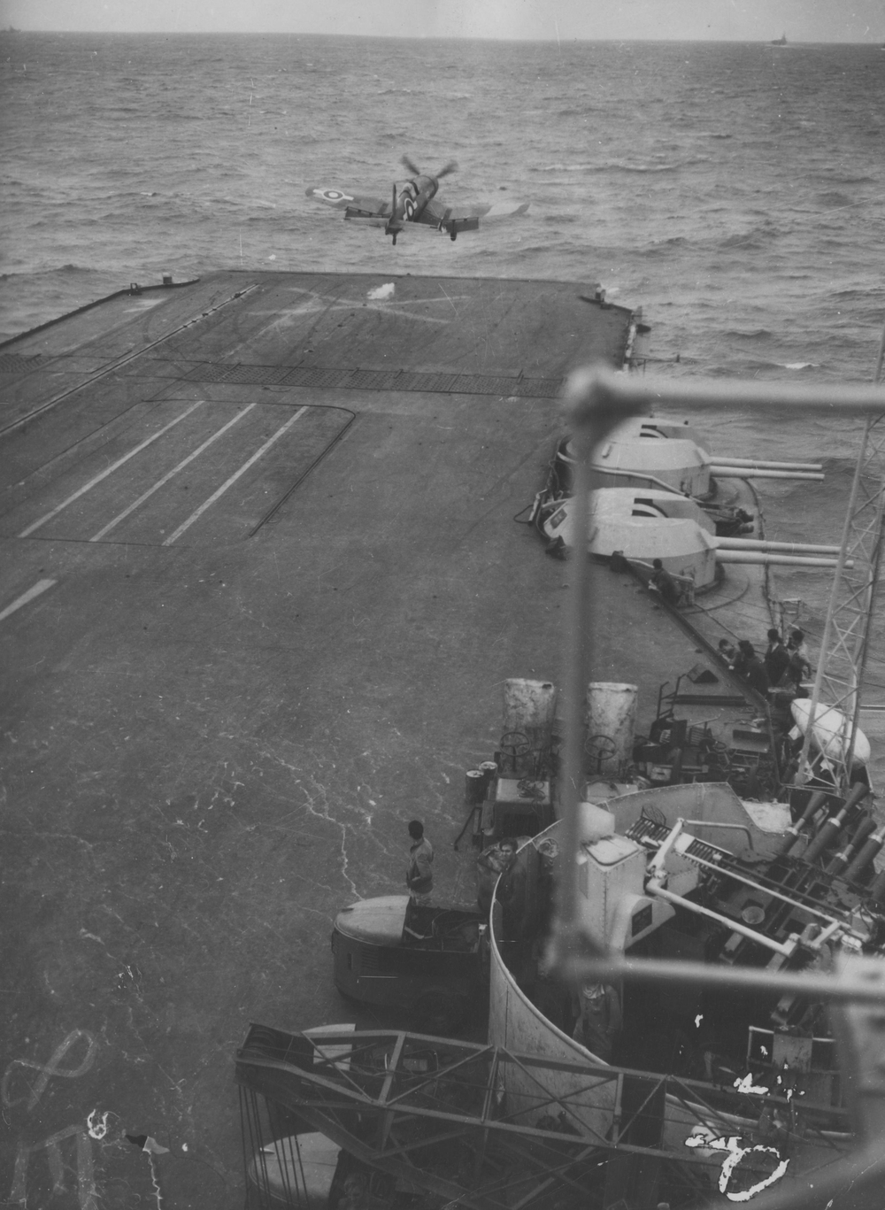 "A Corsair lifts off from HMS ILLUSTRIOUS. Note the aircraft-handling vehicles and ""Jumbo"" crane parked alongside S1 pom pom in the foreground."