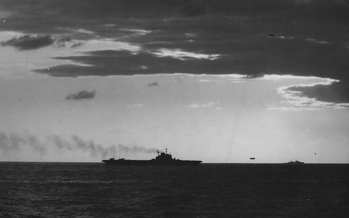HMS VICTORIOUS launches aircraft. The low freeboard betrays this as one of the original three Illustrious class carriers, while the clearly silhouetted director in front of the island is a modification made to HMS VICTORIOUS and FORMIDABLE before the Sakishima operation. The position of the radar mast reveals this to be VICTORIOUS.