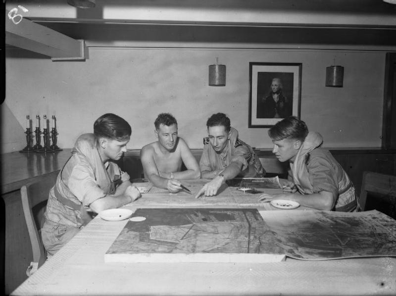 HMS ILLUSTRIOUS' FAA Avenger crews examine intelligence information before a strike.