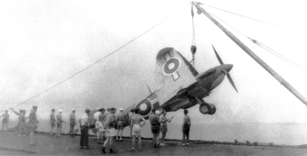 A Seafire is hoisted aboard one of the BPF's replenishment / escort carriers.
