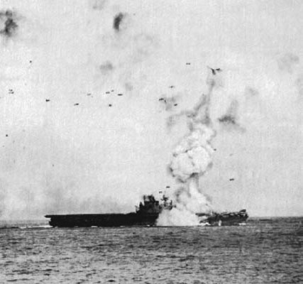 USS Enterprise's forward lift is blasted high into the sky after the impact of a Kamikaze and its 550lb bomb.