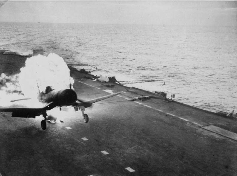 On board a British Pacific fleet carrier operating against the Japanese. Lieutenant Commander (A) Freddy Charlton, British Fleet Air Arm pilot, had a remarkable escape when the long-range petrol tank of his Chance-Vought Corsair fighter burst into flames (seen here) as he landed on the deck of the aircraft carrier. Both pilot and plane escaped damage.
