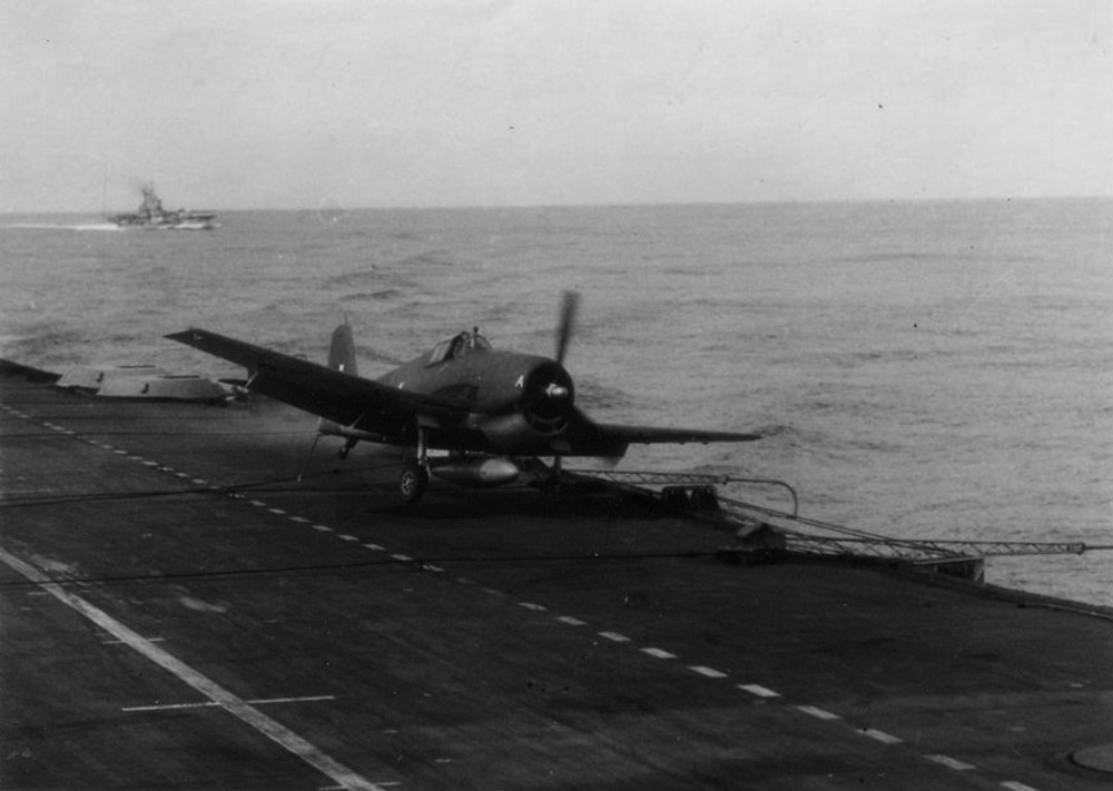 One of HMS INDOMITABLE'S Hellcats swerves towards the deck-edge after grabbing a wire.