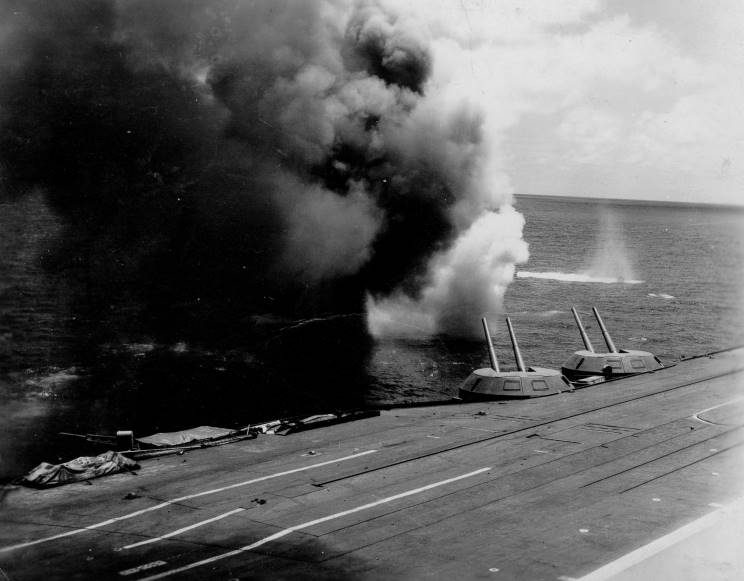The second in a sequence of photographs taken from the bridge of HMS Indomitable showing a kamikaze exploding in the water off the port bow of the armoured aircraft carrier.