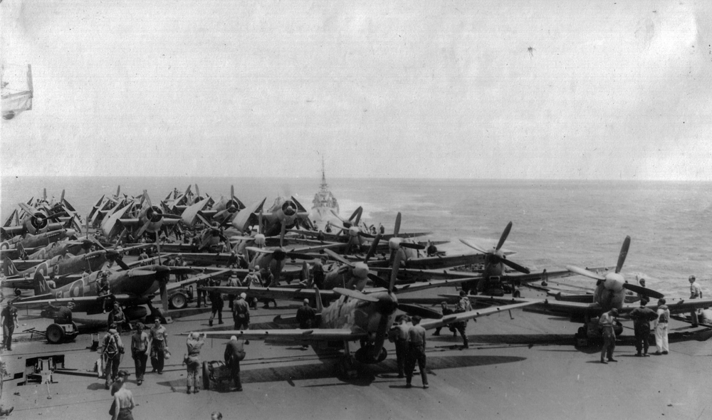 "Seafires and Avengers are ranged for a strike aboard HMS IMPLACABLE. This carrier did not arrive until after the Sakishima campaign. Her Seafires can be identified by the large tear-drop drop tanks adapted from RAAF Kittyhawk stocks. HMS INDEFATIGABLE'S Seafires used the RAF's conformal ""slipper"" style."
